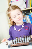 Cute, blonde girl playing chess Stock Photography