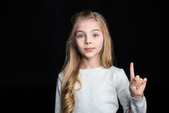 Cute blonde girl. Pointing up with finger on black stock photos