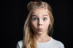 Cute blonde girl. Cute preteen blonde girl grimacing isolated on black Stock Photography