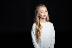 Cute blonde girl. Cute blonde preteen girl looking at camera on black Stock Image