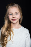 Cute blonde girl. Cute preteen blonde girl smiling at camera on black royalty free stock photo
