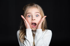 Cute blonde girl. Cute shocked blonde girl looking at camera on black royalty free stock images