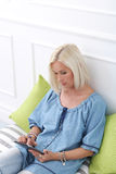 Cute, blonde girl with tablet Royalty Free Stock Photography