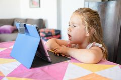 Cute blonde girl watching digital tablet on table of living room at home and complaining expression face. Portrait of four years old blonde cute girl watching royalty free stock photos