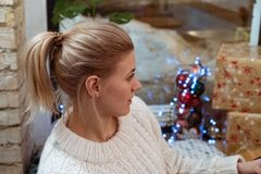 Cute blonde girl in white sweater siting in a cafe royalty free stock image