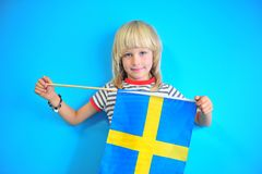 Cute blonde hair kid holding flag of Sweden royalty free stock photo