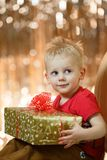 Cute blonde hair little boy keeps a gift.  Royalty Free Stock Photography