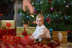 Cute blonde hair little boy near the fireplace and gifts under Christmas tree Royalty Free Stock Photography
