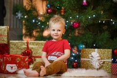 Cute blonde hair little boy near the fireplace and gifts under Christmas tree Royalty Free Stock Images