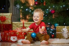 Cute blonde hair little boy near the fireplace and gifts under Christmas tree Stock Photography