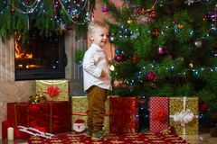 Cute blonde hair little boy near the fireplace and gifts under Christmas tree Royalty Free Stock Image