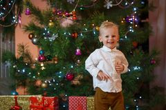 Cute blonde hair little boy near the fireplace and gifts under Christmas tree Stock Photos