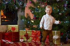 Cute blonde hair little boy near the fireplace and gifts under Christmas tree Stock Photo