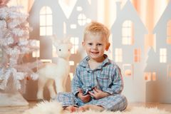 Cute blonde hair little boy in sleepwear near christmas toy paper houses.  Stock Photography