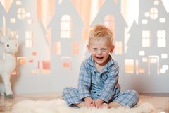 Cute blonde hair little boy in sleepwear near christmas toy paper houses.  Stock Images