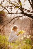 Cute blonde happy little girl with yellow daffodils in the spring country royalty free stock photo