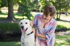 Cute blonde with her labrador dog in the park Royalty Free Stock Photos