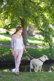 Cute blonde with her labrador dog in the park Royalty Free Stock Photo