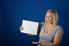 Cute Blonde holding blank sign. Cute young blonde holding up a blank sign ready for your text Royalty Free Stock Images