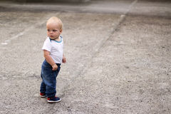 Cute blonde kid looking looking back. Awesome baby boy on the walk. Copy space Royalty Free Stock Photos