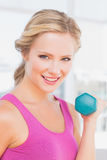 Cute blonde lifting dumbbells and smiling at camera Royalty Free Stock Photography
