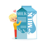 Cute blonde little boy and funny milk carton box with smiling human face playing and having fun, healthy childrens food Royalty Free Stock Image
