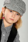 Cute blonde little girl in checked cap Royalty Free Stock Images