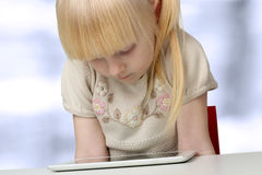 Cute  blonde little girl with digital tablet Royalty Free Stock Image