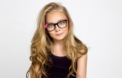 Cute blonde little girl in glasses on a white background in the stock photo
