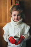 Cute blonde little girl holding hot steaming tea cup close up photo Royalty Free Stock Image