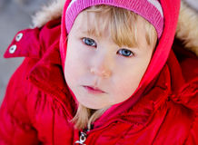 Cute blonde little girl in a red jacket Royalty Free Stock Photos