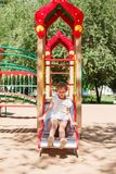 Little girl is sliding at playground Royalty Free Stock Photo