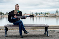 Cute blonde playing guitar while sitting on a bench Royalty Free Stock Photos
