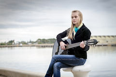 Cute blonde playing guitar while sitting on the bitt Royalty Free Stock Photo
