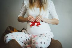 Cute blonde pregnant woman in spotted pyjamas is sitting on the bean bag chair. She is holding small red socks near her belly. royalty free stock photo