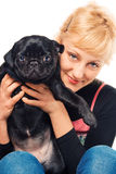 Cute blonde with a pug puppy. Cute blonde holding and kissing a pug Stock Images