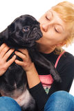 Cute blonde with a pug puppy. Cute blonde holding and kissing a pug Royalty Free Stock Image