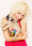 Cute blonde with a pug puppy. Cute blonde hugging a pug puppy Royalty Free Stock Photography