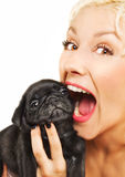 Cute blonde with a pug puppy. Cute blonde playing with a pug puppy Royalty Free Stock Photo