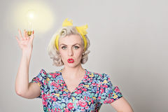 Cute blonde retro girl holding glowing light bulb - humorous con Stock Photo