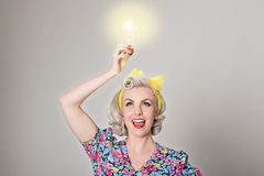 Cute blonde retro girl holding glowing light bulb - humorous con Stock Photography