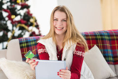 Cute blonde sitting on couch holding credit card and tablet Royalty Free Stock Image