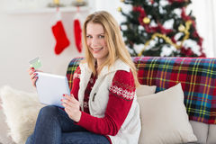 Cute blonde sitting on couch holding credit card and tablet Stock Photography
