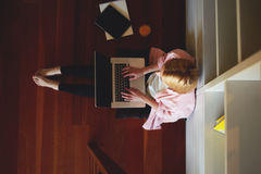 Cute blonde sitting on the floor on his knees is a computer, she looks mail Stock Photos