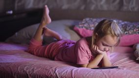 Cute blonde small girl dressed in pink pyjamas is lying in bed and watching cartoons with smartphone. Toddler female kid