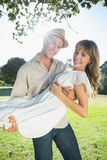 Cute blonde smiling while being picked up by boyfriend in the park Royalty Free Stock Photography