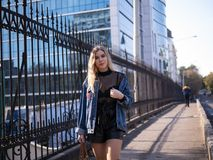 Cute blonde teen with flowing hair in a denim jacket on the bridge outdoor stock image