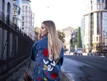 Cute blonde teen with flowing hair in a denim jacket on the bridge outdoor