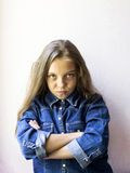 Cute blonde teen girl with a cunning look. On a light background Royalty Free Stock Image