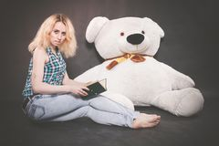 Cute blonde teen in jeans and plaid shirt plays with her huge Teddy polar bear in yellow scarf on black background. Alone stock photo